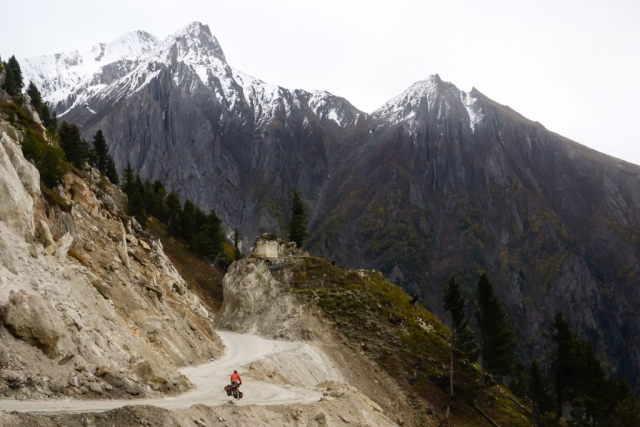 Snow falls as a cyclist tackles the final pass of the Himalayas on the Leh-Srinigar road.